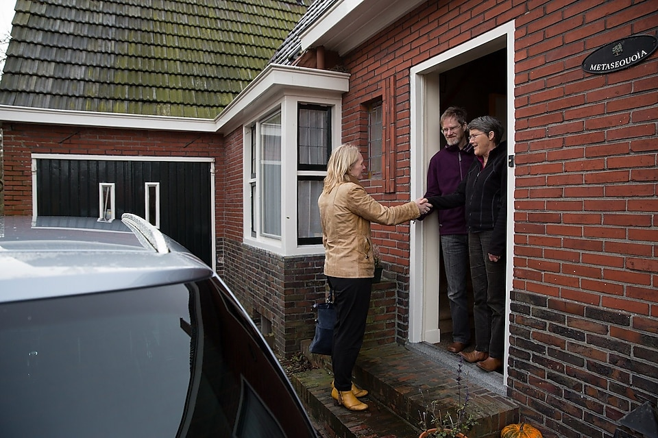 lady hand shaking with two men at entrance of house